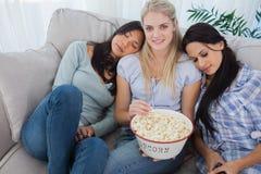 Друзья дремая на белокурых друзьях взваливают на плечи еду попкорна Стоковые Изображения
