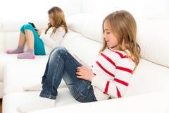 Друзья сестры ягнятся девушки играя с ПК таблетки в софе Стоковая Фотография