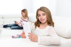 Друзья сестры ягнятся девушки играя с ПК таблетки в софе Стоковые Фотографии RF