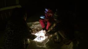 Друзья сидя вокруг огня держа ручки при еда, проверяя карту на таблетке видеоматериал