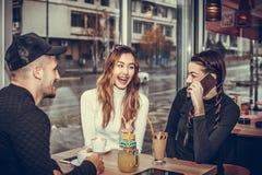 Друзья сидя в кафе и говорить Стоковые Фото