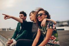 Друзья сидя на крыше и наслаждаясь взглядом Стоковые Фото