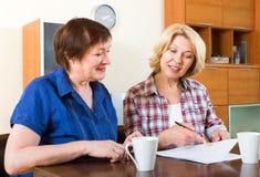 Друзья сидя на столе и подписывая контракте Стоковое Изображение
