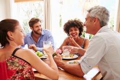 Друзья сидя на таблице говоря во время официальныйа обед стоковое фото