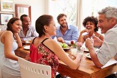 Друзья сидя на таблице говоря во время официальныйа обед стоковое фото rf