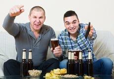 Друзья сидя на таблице с пивом Стоковые Фото