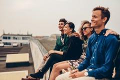 Друзья сидя совместно на крыше стоковая фотография