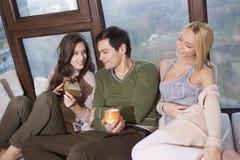 Друзья сидя совместно на софе имея потеху Стоковое Изображение RF