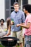 Друзья скрепляя над bbq с пив в руке стоковое изображение