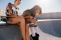 Друзья смеясь над и наслаждаясь на парке конька Стоковые Фотографии RF