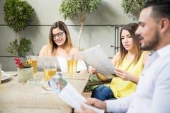 Друзья смотря меню ресторана Стоковые Фотографии RF