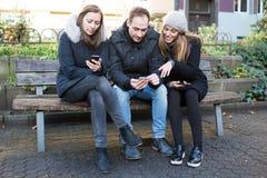 Друзья смотря на телефоне на скамейке в парке Стоковое Фото