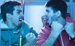 Друзья смотря спорт на ТВ стоковое фото