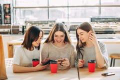 Друзья смотря умный телефон сидя в кафе Стоковая Фотография