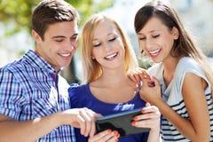 Друзья смотря цифровую таблетку Стоковые Изображения