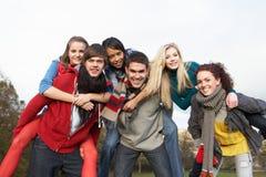 друзья собирают иметь езды piggyback подростковые Стоковое Изображение