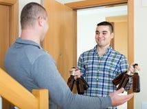 Друзья собирая для того чтобы выпить пиво дома Стоковая Фотография RF