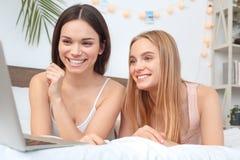 Друзья совместно дома лежа на кровати смотря фильм на конце-вверх ноутбука жизнерадостном стоковые фотографии rf