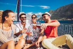 Друзья со стеклами шампанского на яхте Каникулы, перемещение, море, приятельство и концепция людей стоковые фото