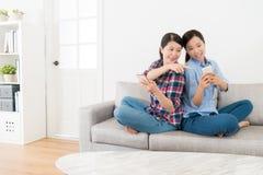 Друзья спина к спине сидя на софе живущей комнаты Стоковая Фотография