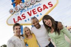 Друзья стоя совместно против «гостеприимсво к знака Лас-Вегас» стоковые фотографии rf