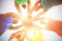 Друзья стоя с штабелированными руками против неба Стоковые Фото
