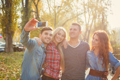 Друзья сфотографированы с smartphone в парке Стоковое Фото