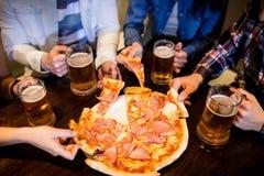 Друзья с кружкой и пиццей пива в баре Стоковое Фото