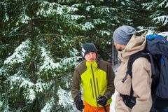 Друзья с рюкзаками в лесе в зиме Стоковые Фотографии RF