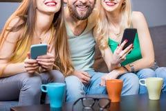 Друзья с телефонами дома Стоковые Изображения