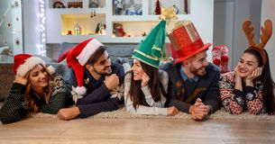 Друзья с шляпами рождества наслаждаясь совместно Стоковое Изображение