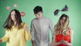 Друзья танцуют в красочном confetti на зеленой предпосылке акции видеоматериалы