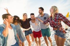 Друзья танцуя на пляже стоковое изображение