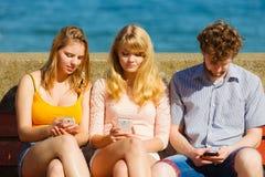 Друзья укомплектовывают личным составом и женщины используя мобильные телефоны Стоковое Изображение