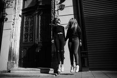 Друзья усмехаясь и идя в старый город стоковое фото