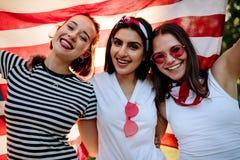 Друзья усмехаясь с американским флагом Стоковое Изображение