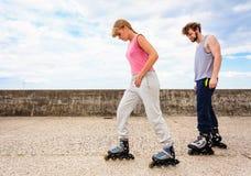 Друзья учат что rollerblading совместно имейте потеху на парке Стоковое фото RF