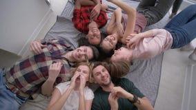 Друзья щекочут один другого пока лежащ на их задних частях и смеющся весело на камере во время домашней партии видеоматериал