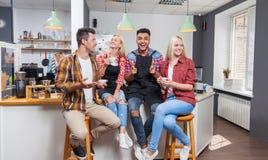 Друзья людей выпивая смеяться над кофейни говоря при barista сидя на счетчике бара Стоковое Изображение