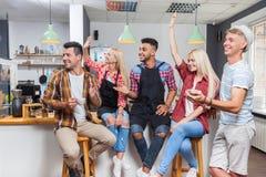 Друзья людей выпивая смеяться над кофейни говоря при barista сидя на счетчике бара, человеке гонки смешивания и женщине счастливы Стоковые Фотографии RF