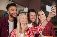 Друзья людей принимая фото Selfie на счетчик бара, телефон владением женщины человека гонки смешивания умный стоковые фото