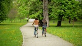 Друзья Active усмехаясь женские с темными волосами в куртках и джинсах едут на велосипедах Задний взгляд 2 милого сток-видео