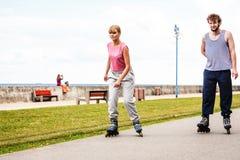 Друзья rollerblading совместно имеют потеху в парке Стоковые Изображения