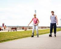 Друзья rollerblading совместно имеют потеху в парке Стоковое Изображение RF