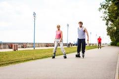 Друзья rollerblading совместно имеют потеху в парке Стоковые Фото