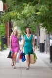 Друзья Shopaholic женские идя на тротуар Стоковая Фотография
