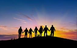 Друзья silhouette держать рука об руку стоковая фотография
