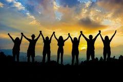 Друзья silhouette держать рука об руку стоковое фото