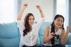 2 друз азиатских женщин конкурсных играя видеоигры и exci Стоковое фото RF