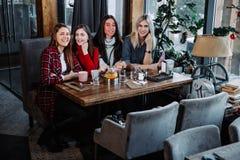 4 друз в кафе смотрят камеру и смеются над Стоковое Изображение